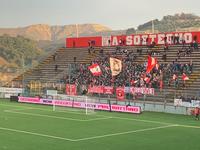 Scatto della curva dei tifosi del Teramo Calcio con banner luminoso a bordocampo con la scritta
